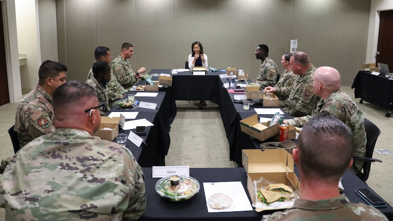 Men and women sitting around a table having lunch