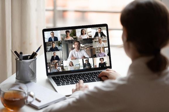 woman looks at a laptop screen display showing 14 other individuals in a virtual meeting