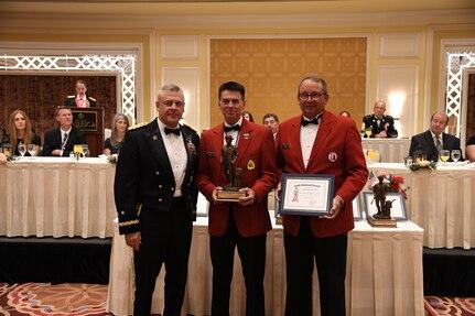 Maj. Gen. (Ret.) Jeff Burton (center), the previous adjutant general of the Utah National Guard, receives the Bronze Minuteman award