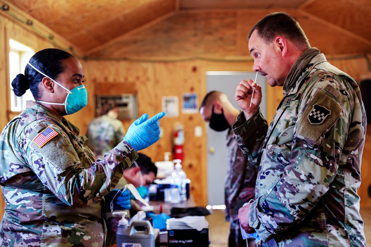 A female soldier wearing a face mask and gloves points a finger and watches as another soldier, whose face mask is pulled down beneath his chin, swabs his nose.