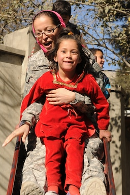 U.S. 1st Lt. Ana Monteiro, 1st Battalion, 101st Field Artillery Regiment (1-101st), Massachusetts Army National Guard, goes down a slide with an Afghan girl at Arian School during a humanitarian aid drop of school supplies on Nov. 10, 2010, in Kabul, Afghanistan. Monteiro and other Soldiers of the 1-101st have 'adopted' the mostly girl school by providing three more classrooms and donating school supplies several times since May