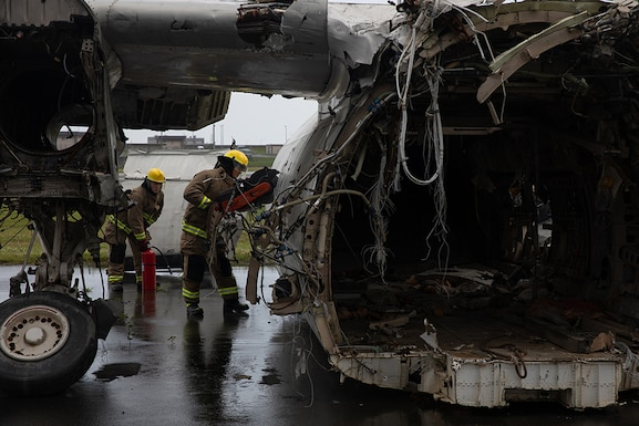 Firefighters cut into the side of a scrapped airplane.
