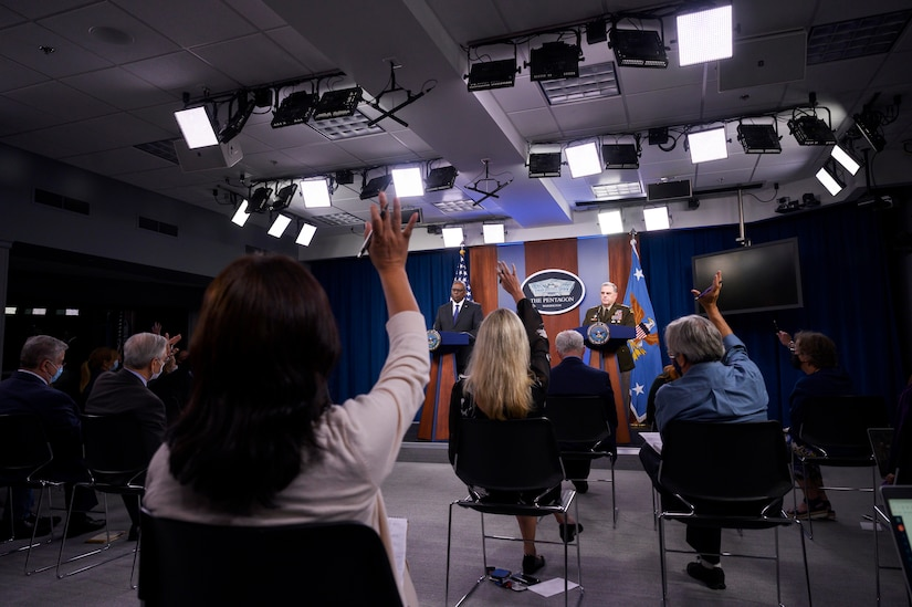 Secretary of Defense Lloyd J. Austin III and Joint Chiefs Chairman Army Gen. Mark A. Milley stand at a podium while reporters raise hands.