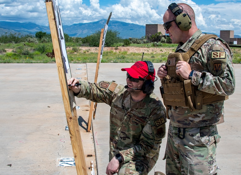 A photo of two airmen on a firing range