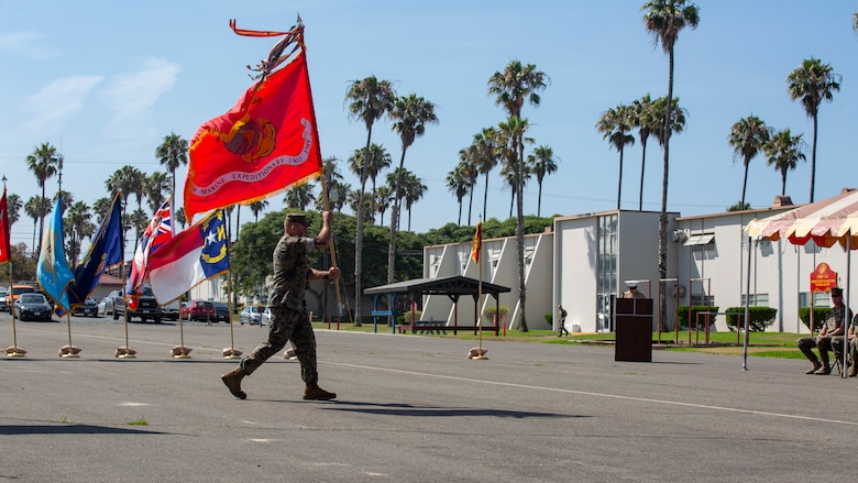 U.S. Marine Corps Master Gunnery Sgt. Jamie Myers, operations chief, 15th Marine Expeditionary Unit, carries the unit colors during a change of command ceremony at Marine Corps Base Camp Pendleton, California, July 21, 2021