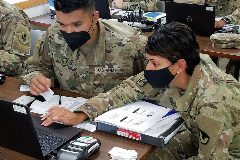 Master Sgt. Eva Miranda, U.S. Army Financial Management Command Operational Support Team senior financial management systems instructor, helps Soldiers use financial management tactical platforms, or FMTPs, during Diamond Saber at Fort McCoy, Wisconsin, Aug. 14, 2021. Diamond Saber is a U.S. Army Reserve-led exercise that incorporates participation from all components and joint services, and it prepares finance and comptroller Soldiers on the warfighting functions of funding the force, payment support, disbursing operations, accounting, fiscal stewardship, auditability and data analytics. (U.S. Army photo by Mark R. W. Orders-Woempner)