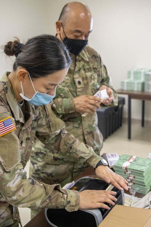 Spc. Saralin Moon, 326th Financial Management Support Center disbursing technician, and Lt. Col. Luke Ahn, 326th FMSC disbursing officer, count simulated money after moving their operation in less than two hours during Diamond Saber at Fort McCoy, Wisconsin, Aug. 14, 2021. Diamond Saber is a U.S. Army Reserve-led exercise that incorporates participation from all components and joint services, and it prepares finance and comptroller Soldiers on the warfighting functions of funding the force, payment support, disbursing operations, accounting, fiscal stewardship, auditability and data analytics. (U.S. Army photo by Mark R. W. Orders-Woempner)