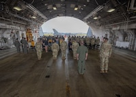 Airmen stand at attention during arrival of official party in hanger.