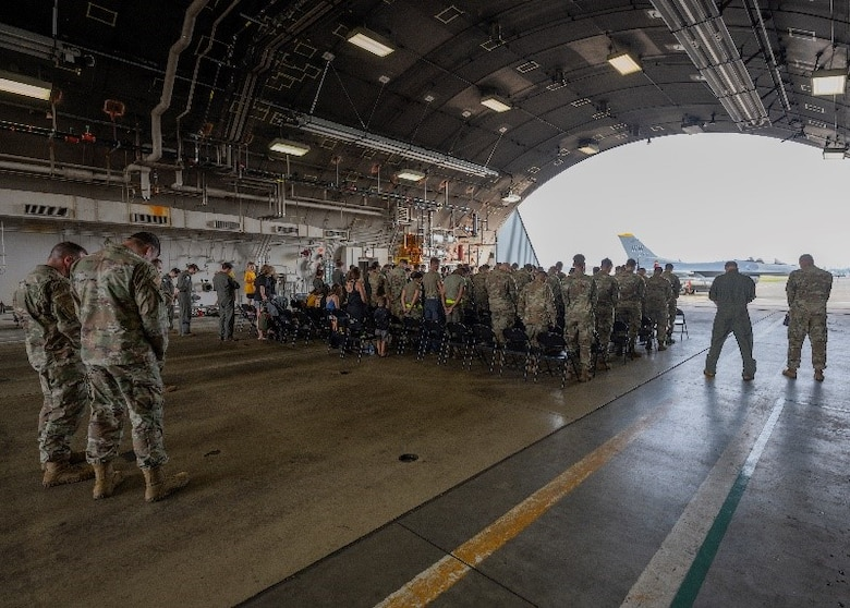 Airmen and families listening to an invocation during a ceremony in a hanger.