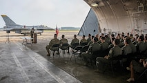 Airmen in a hanger attending a ceremony with fighter jet in the background.