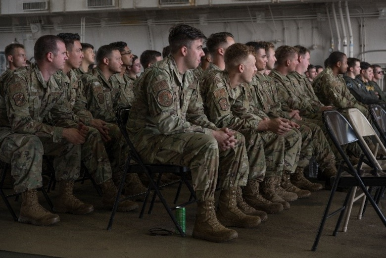Military members sitting in a row of chairs at a ceremony in a hanger.