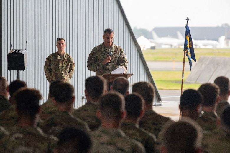 Military member address a hangar full of people during a ceremony.