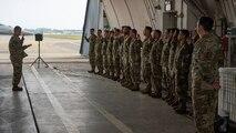 Twenty-three military members raise right hand and recite an oath.