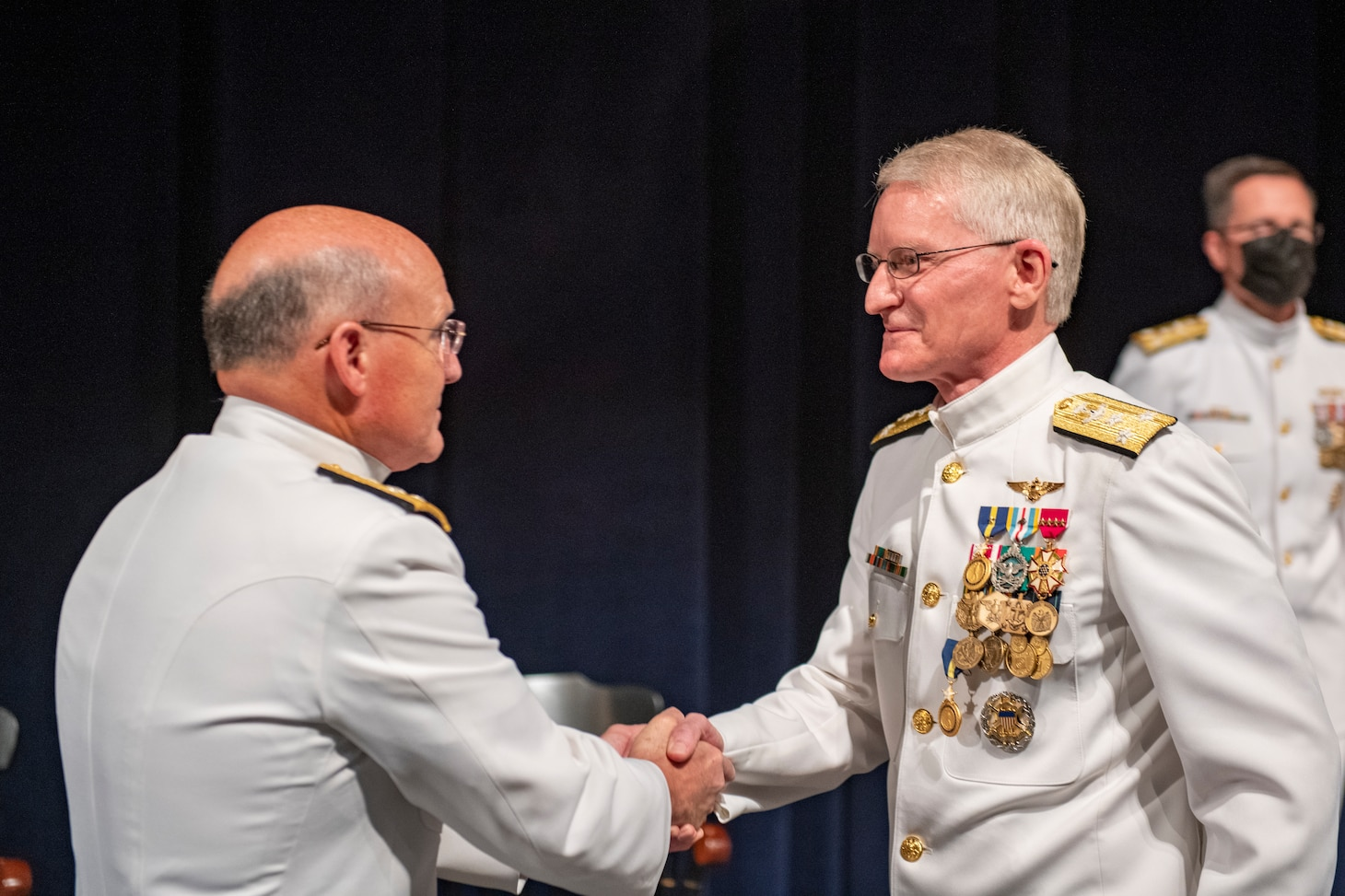 Chief of Naval Operations Adm. Mike Gilday, left, shakes the hand of Vice Adm. John G. Hannink during a change of office ceremony at the U.S. Naval Academy.