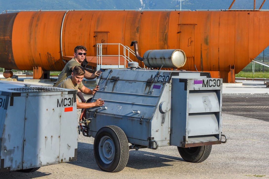 Senior Airman Hunter Clark, left, and Senior Airman Jarrett Janak, 31st Maintenance Squadron (MXS) transient alert journeymen, push equipment in preparation for a Crash, Damaged or Disabled Aircraft Recovery (CDDAR) lift certification at Aviano Air Base, Italy, Aug. 13, 2021. The 31st MXS and 52nd MXS, Spangdahlem Air Base, Germany, participated in an annual CDDAR training to recertify on qualifications. The 31st MXS provides accessory maintenance, avionics, periodic phase inspections, fabrication, and aerospace ground equipment for assigned aircraft. (U.S. Air Force photo by Senior Airman Brooke Moeder)