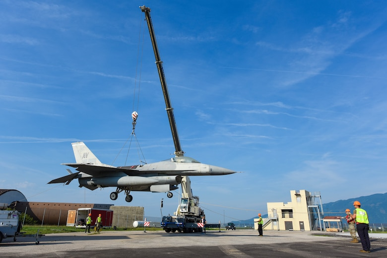 A U.S. Air Force F-16 Fighting Falcon is lifted from the ground during an annual Crash, Damaged or Disabled Aircraft Recovery (CDDAR) lift certification at Aviano Air Base, Italy, Aug. 13, 2021. The purpose of a real-world crash damaged disabled aircraft recovery is to clear the runway as safely and quickly as possible while causing no further damage to the aircraft. (U.S. Air Force photo by Senior Airman Brooke Moeder)