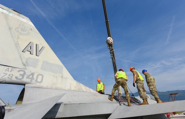 U.S. Airmen assigned to the 31st Maintenance Squadron (MXS) and 52nd MXS attach a crane to a U.S. Air Force F-16 Fighting Falcon at Aviano Air Base, Italy, August 13, 2021. The Airmen participated in an annual Crash, Damaged or Disabled Aircraft Recovery (CDDAR) lift certification to recertify on the correct procedures of lifting an aircraft during an emergency. The purpose of a real-world crash damaged disabled aircraft recovery is to clear the runway as safely and quickly as possible while causing no further damage to the aircraft. (U.S. Air Force photo by Senior Airman Brooke Moeder)