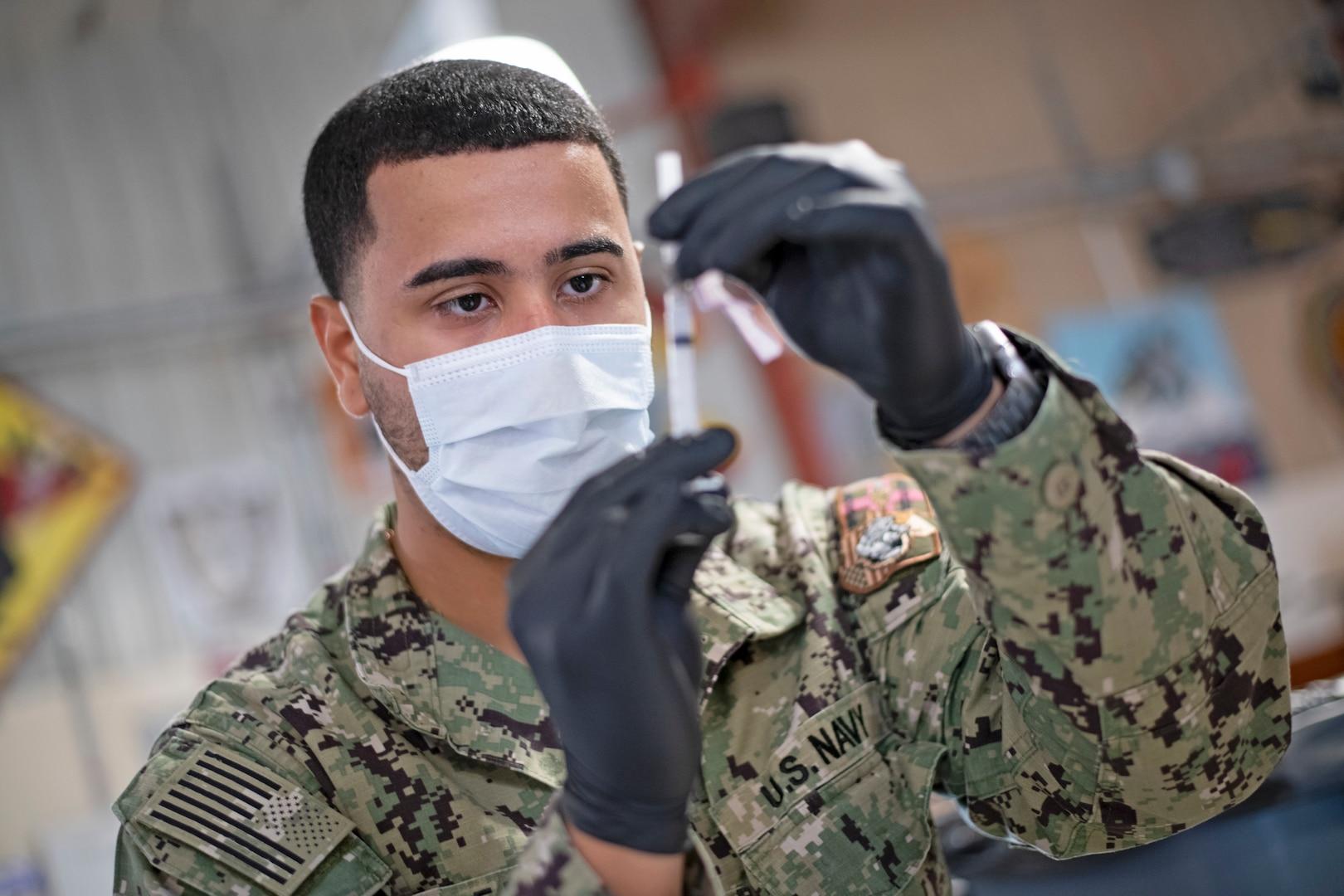 Service member prepares COVID-19 vaccine supplies