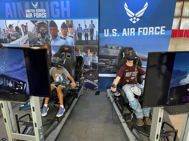 Two students compete with a flight simulator game sponsored by the U.S. Air Force Recruiting Service Detachment 1 at the Experimental Aircraft Association (EAA) AirVenture Air Show at Oshkosh, Wis., July 26, 2021.
