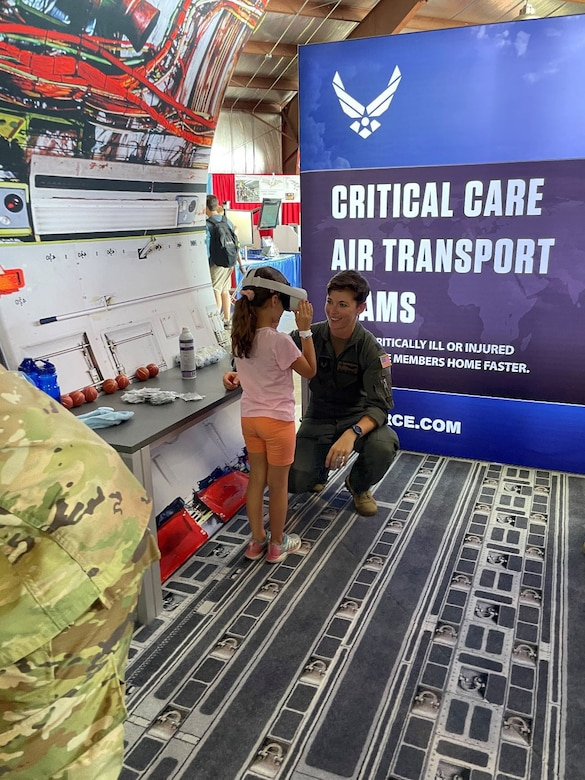 Capt. Blaine Driscoll, a U-28 Combat Systems Officer assigned to the 318th Special Operations Squadron, shows a student attending the Experimental Aircraft Association (EAA) AirVenture Air Show what an experience it is to operate an F-22 Raptor from the perspective of a 360 degree video through a virtual reality headset at Oshkosh, Wis., July 26, 2021.