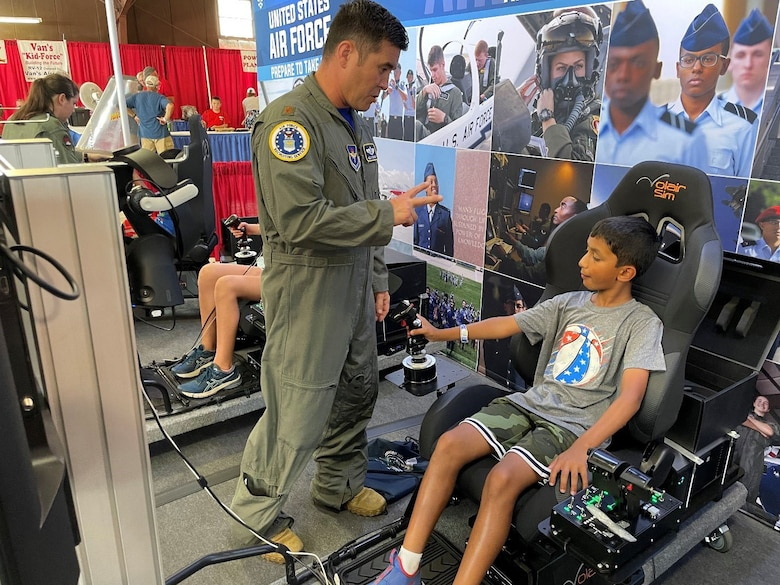 Maj. Kelly McNerney with Air Force Recruiting Service Detachment 1, instructs a student attending the Experimental Aircraft Association (EAA) AirVenture Air Show on the best practices for operating the flight simulator at Oshkosh, Wis., July 26, 2021.