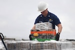 Lt. William Singletary, operations officer aboard the Cutter Eagle, moving pallets summer 2021. U.S. Coast Guard photo.