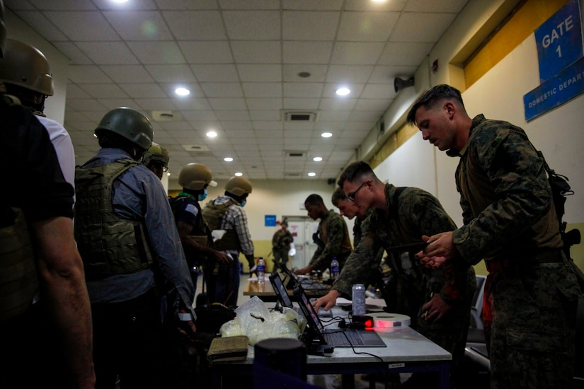 Marines stand behind a table with laptops and speak to personnel standing in a line wearing security gear.