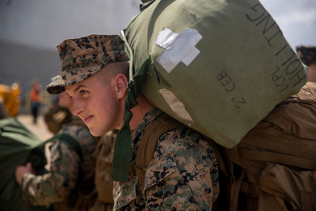 U.S. Marine Corps Cpl. Jack Hollings, a Loveland, Colo., native and a combat engineer from 1st Battalion, 6th Marine Regiment, 2d Marine Division, loads onto the USS Arlington (LPD-24) on Naval Station Norfolk, Va. Aug. 17, 2021. The Marines from 1/6 are loading in preparation to deploy in support of Joint Task Force Haiti during their humanitarian assistance disaster relief mission. (U.S. Marine Corps photo by Lance Cpl. Jacqueline Arre)