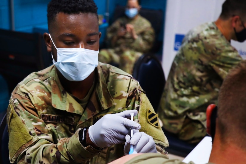 A soldier wearing a face mask and gloves holds a syringe while giving another soldier  a vaccine.