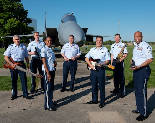 Members of the Air Force Band of Flight's rock ensemble Flight One pose May 14, 2021, in front of an F-15 Eagle fighter on display at the National Museum of the U.S. Air Force on Wright-Patterson Air Force Base, Ohio. (U.S. Air Force photo by R.J. Oriez)