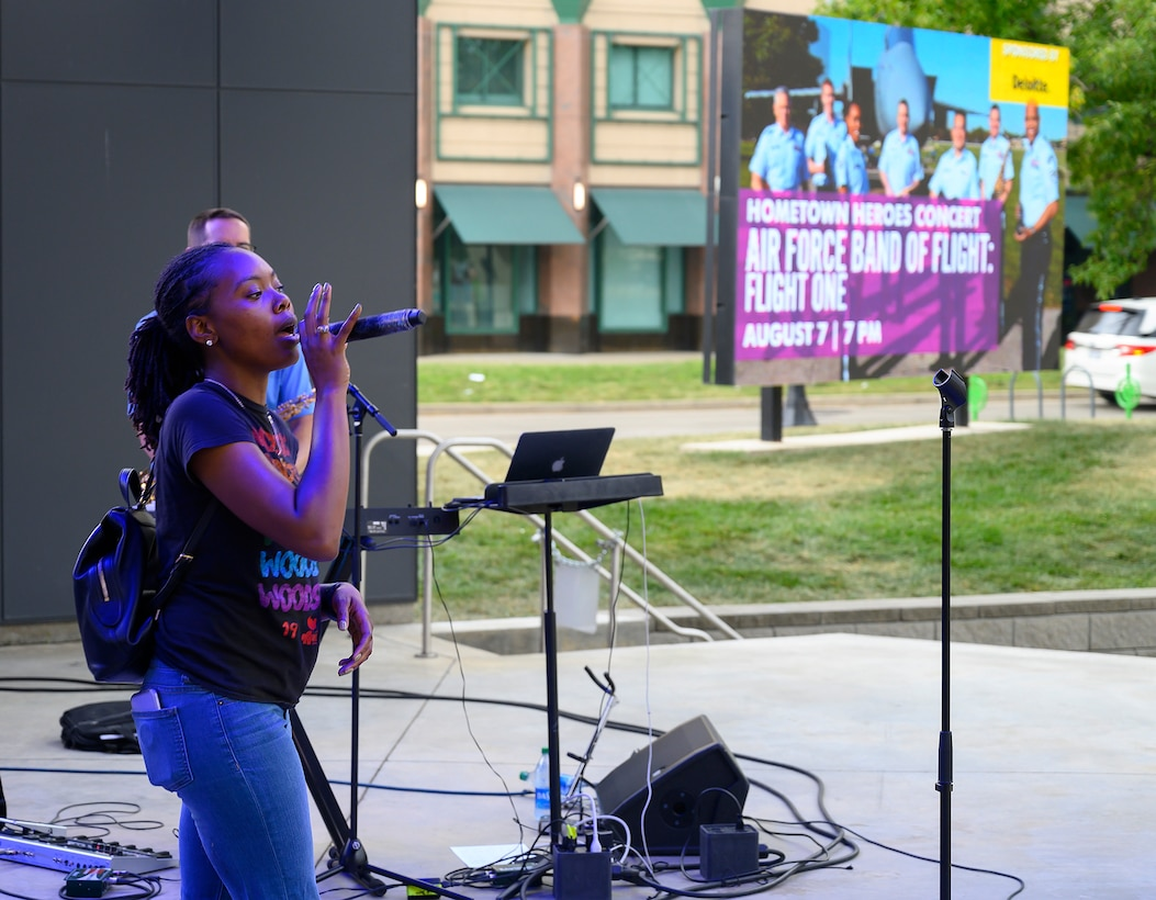 Senior Airman MeLan Smartt, Air Force Band of Flight's Flight One vocalist, does her sound check on the stage of Levitt Pavilion in Dayton, Ohio, the afternoon of Aug. 7, 2021, as an electronic billboard advertises that night's show.  (U.S. Air Force photo by R.J. Oriez)