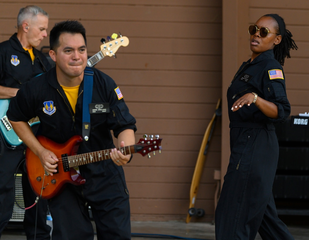 Airman 1st Class Christopher Arellano (foreground), Tech. Sgt. Joseph Whitt and Senior Airman MeLan Smartt jam during a performance of Flight One, an Air Force rock band, on Aug. 13, 2021, at Centerville Community Amphitheater in Stubbs Park, Centerville, Ohio. (U.S. Air Force photo by R.J. Oriez)