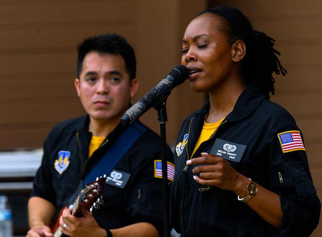 """Senior Airman MeLan Smartt and Airman 1st Class Christopher Arellano perform the Etta James classic """"At Last"""" at Centerville Community Amphitheater in Stubbs Park, Centerville, Ohio, on Aug. 13, 2021, as part of a concert by Flight One, the Air Force Band of Flight rock ensemble stationed at Wright-Patterson Air Force Base. (U.S. Air Force photo by R.J. Oriez)"""