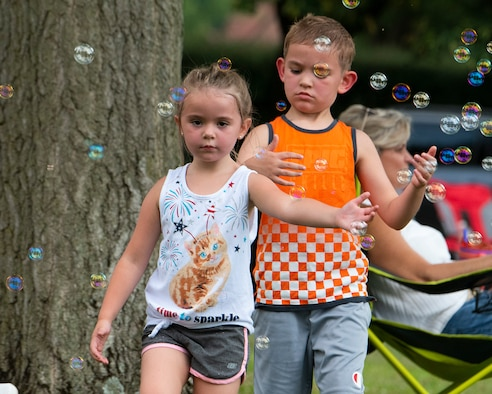 Lily, 5, and Skyler, 7, the children of 1st Lt. Brandon and Amber McVey, play amongst the bubbles at a block party Aug. 12, 2021, put on by the 88th Force Support Squadron in the historic Brick Quarters housing area at Wright-Patterson Air Force Base, Ohio. The party was the middle in a summer series of three sponsored by 88 FSS for Wright-Patt community members. (U.S. Air Force photo by R.J. Oriez)