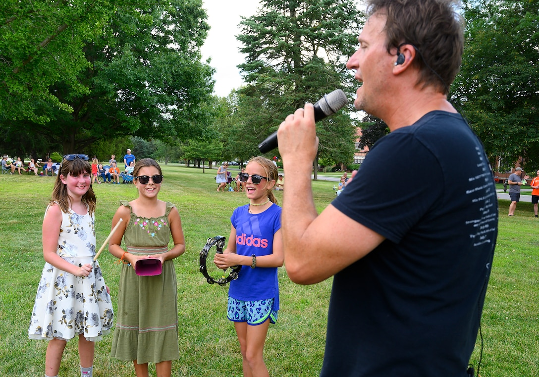 eff Stevens, lead singer for Stranger, gets (from left) Amelia Hunter, 9, Ella Arnold, 11, and Hannah Greiner, 10, to accompany him on a song as he and his band perform at a block party Aug. 12, 2021, put on by the 88th Force Support Squadron in the historic Brick Quarters housing area at Wright-Patterson Air Force Base, Ohio. This was the second of three parties this summer, with the last one scheduled for Aug. 26. (U.S. Air Force photo by R.J. Oriez)