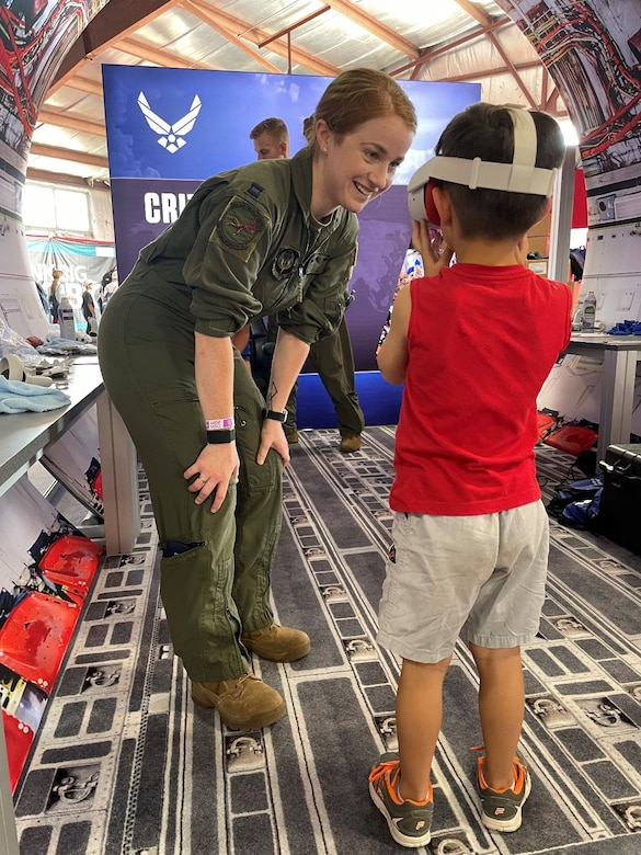 An RPA pilot, shows a student attending the Experimental Aircraft Association (EAA) AirVenture Air Show what an experience it is to operate an F-16 Fighting Falcon from the perspective of a 360 degree video through a virtual reality headset at Oshkosh, Wis., July 26, 2021.