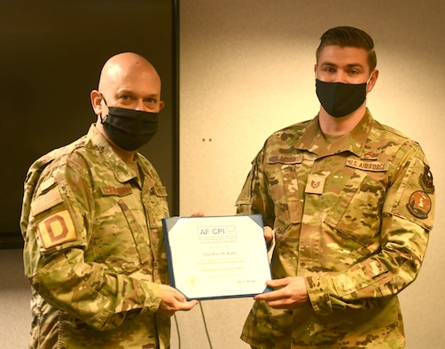 U.S. Air Force Senior Master Sgt. Stephen Holdenried, 100th Air Refueling Wing Continuous Process Improvement process manager presents a framed copy of a Green Belt certification project to U.S. Air Force Tech. Sgt. Ross Kahle, 373rd Training Squadron, Detachment 19 Aerospace Ground Equipment instructor, at Royal Air Force Mildenhall Aug. 18, 2021. Kahle instigated the project and put together a team to find issues and solve problems in his training squadron as part of his certification process, enabling him to become fully certified in Green Belt training. (U.S. Air Force photo by Tech. Sgt. Mackenzie Mendez)