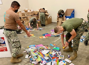 """LEMOORE, Calif. (Aug. 20, 2021) Sailors and Marines at the Center for Naval Aviation Technical Training Unit Lemoore sort through school supplies as part of their """"Backpack Brigade""""  effort to give local and military families school supplies for the 2021 school year. (U.S. Navy photo)"""