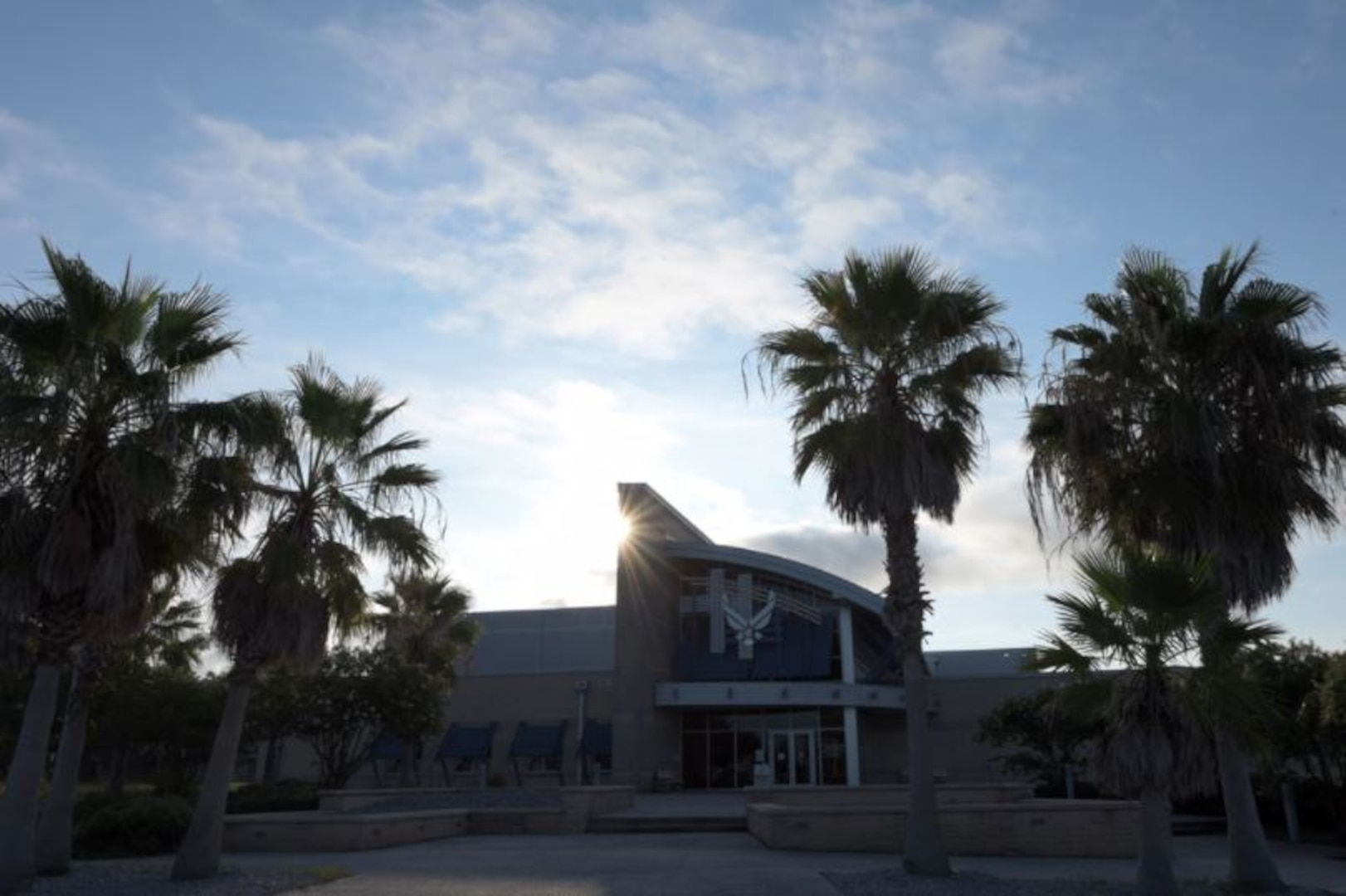 The sun rises behind the Fitness Center at Tyndall Air Force Base, Florida, Aug. 6, 2021. The Fitness Center adjusted operating hours to comply with Health Protection Condition CHARLIE to allow for deep sanitation of the facility and has limited access to manned-hours only. (U.S. Air Force photo by Staff Sgt. Magen M. Reeves)