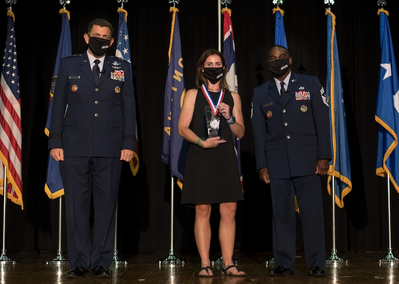 Ms. Jennifer Weir, wife of U.S. Air Force Master Sgt. Tyler Weir, 120th Airlift Wing, Montana National Guard, poses for a photo with Lt. Gen. Michael A. Loh, left, director, Air National Guard (ANG), and Chief Master Sgt. Maurice L. Williams, command chief, ANG, during the Outstanding Airmen of the Year ceremony at Joint Base Andrews, Maryland, Aug. 19, 2021. Master Sgt. Tyler Weir, who passed away in early 2021, was recognized as the ANG's Non-commissioned Officer of the Year during Focus on the Force Week 2021—an annual event hosted by the ANG command chief that highlights professional development and celebrates the accomplishments of the top performing members of the enlisted corps. (U.S. Air National Guard photo by Tech. Sgt. Morgan R. Whitehouse)
