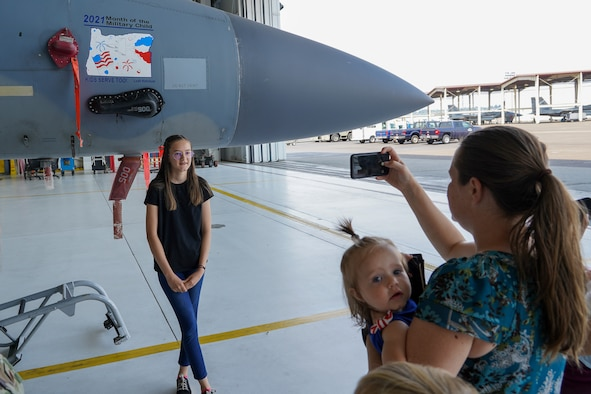 Leah Ketchum poses for a photo in front of a 142nd Wing F-15 Eagle that now displays her artwork on its nose on August 12, 2021 in Portland, Ore. The 142nd Wing and the 173rd Fighter Wing both held contests in support of Month of the Military Child in which each wing chose one winner to have their designs applied to fighter jets at their respective wings. (U.S. Air National Guard Photo by Staff. Sgt. Alexander Frank)