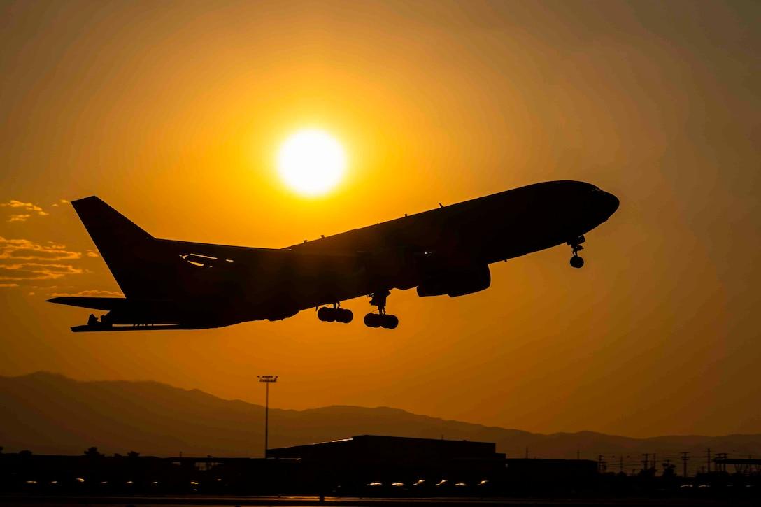 An aircraft flies as the sun shines behind.
