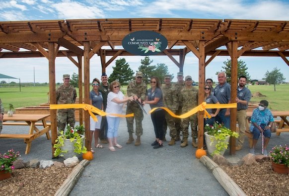 97th Air Mobility Wing members gather for a ribbon cutting ceremony for the opening of the Community Garden at Altus Air Force Base, Oklahoma, Aug. 20, 2021. After the ceremony was finished, individuals who rented plots could officially start planting their gardens. (U.S. Air Force photo by Airman 1st Class Amanda Lovelace)