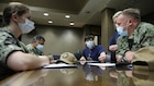 Medical providers from Navy Medicine Readiness and Training Command Bethesda speak with Jacob Smith, the clinical nurse manager at Ochsner Lafayette General Medical Center, during their in- processing for COVID-19 response operations in Lafayette, Louisiana, Aug. 18, 2021.