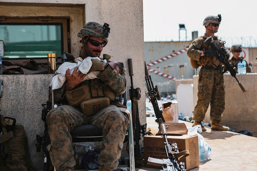 A Marine sits and holds a baby while another stands watch.