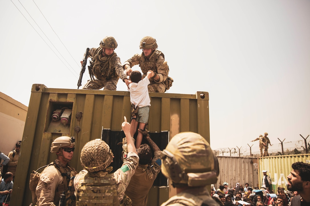 Two service members help life a child onto a truck with help from others on the ground.