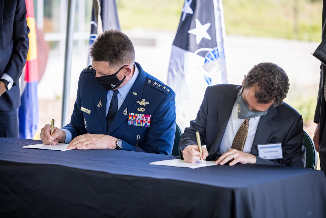 Vice Chief of Space Operations Gen. David D. Thompson and University of Colorado President Todd Saliman sign a Memorandum of Understanding Aug. 20, 2021 at the Ent Center for the Arts Garden at the University of Colorado at Colorado Springs, Colorado. (Photo by Jeffrey M Foster)