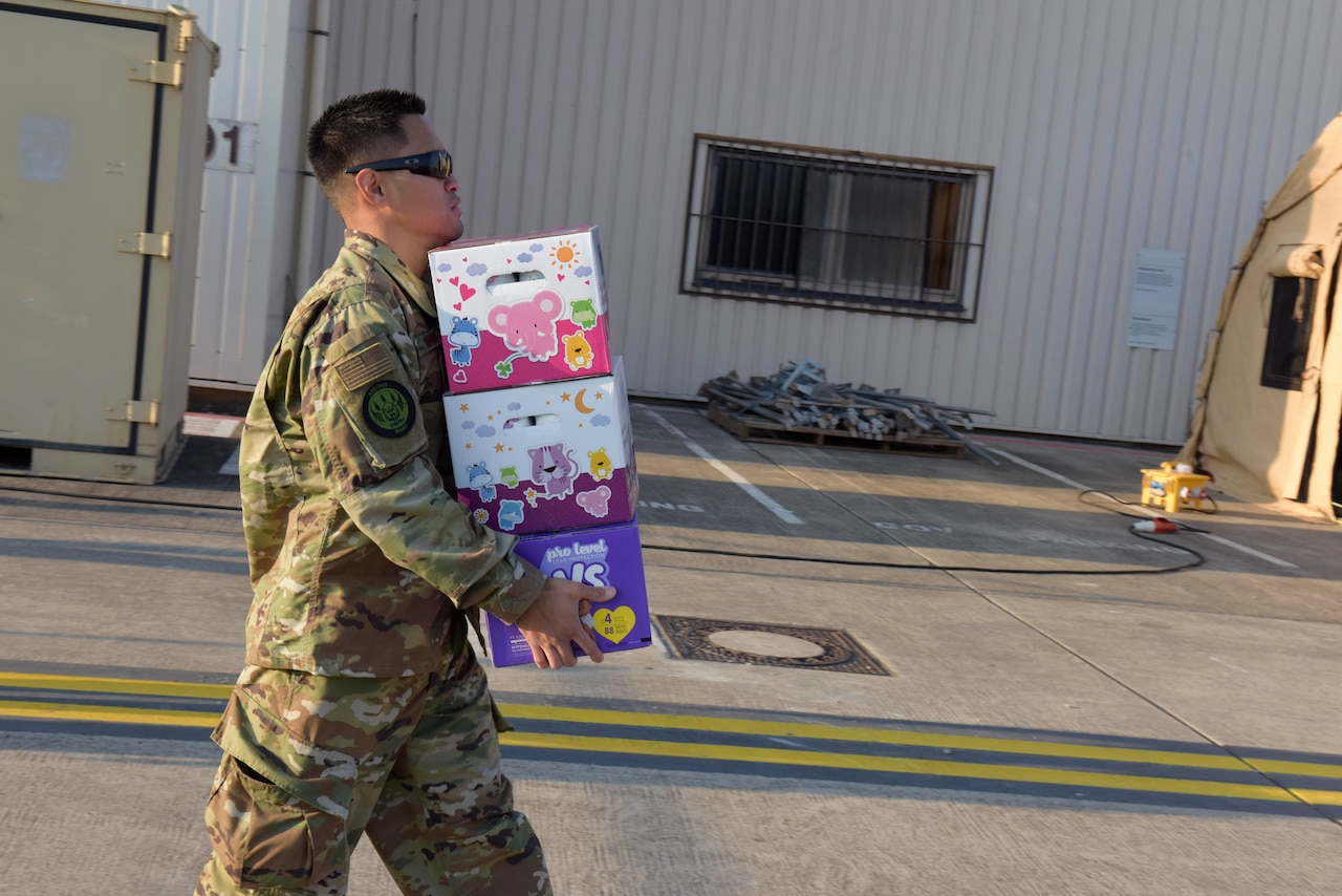 An aiman walks with a handful of boxes.