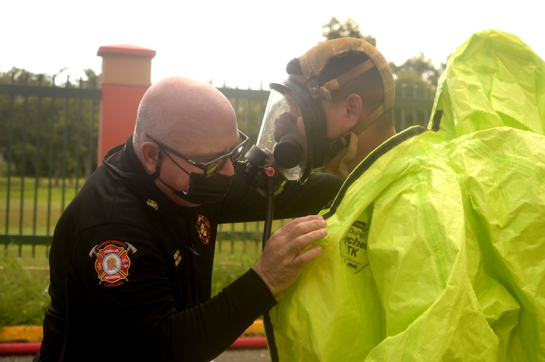 A Weapons of Mass Destruction Civil Support Team member's protective suit is inspected before the member responds to a potential chemical, biological, or radiological threat while participating in a training event in the municipality of Carolina, Puerto Rico, Aug. 18, 2021.