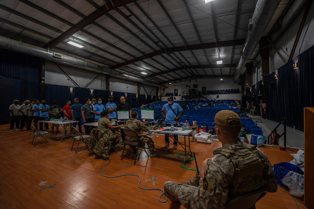 Members from the 379th Air Expeditionary Wing process Afghanistan evacuees at a camp theatre in the CENTCOM region, Aug. 20, 2021.